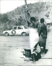 Women doing something while watching the car.