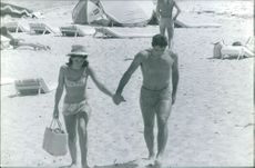 A couple walking on beach holding hands.
