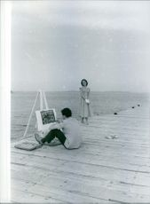 Ulla Jacobsson watching over her husband, Hans Winfried Rohsmann while painting the sea.