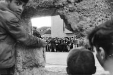 Children are watching through the hole to the people who are being manned by army, 1963