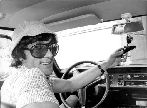 Tennis player Ilie Nastase in his car with a small pair of soccer shoes hanging in the rear mirror