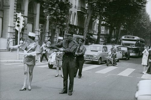 A policeman and policewoman performing on the middle of the road in Paris. 1968