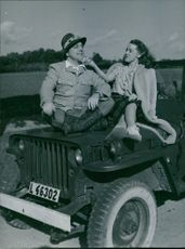 """Sonja Wigertsson and Åke Ohberg sitting at the top of the hood of the jeep as one of the scenes from the movie, """"I love you, Vixen""""."""