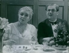 """Erik """"Bullen"""" Berglund and Karin Swanström in a dining table looking at something. A scene for the """"Fasters millioner"""" film in 1934."""