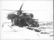 An Army jeep and its personnel drive away from the Sikorsky CH-37B helicopter that brought it to the field