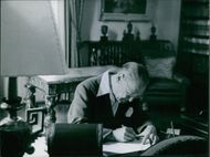 William Somerset Maugham writing at his desk in his office.