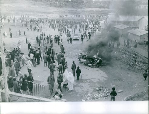 A car was burned with people standing, passing by, looking at the incident, during the war in Algeria, 1960.