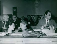 People sitting in a courtroom during a proceeding on the Messina Affair.