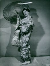 Renata Tebaldi posing in traditional dress, holding umbrella. 1960