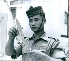 A Gurkha holding a huge knife in his hands while gently touching its blades.
