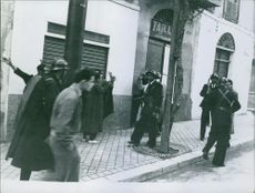 Soldiers with prisoners on side walk.