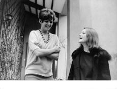Claudia Cardinale giggling with her friend.