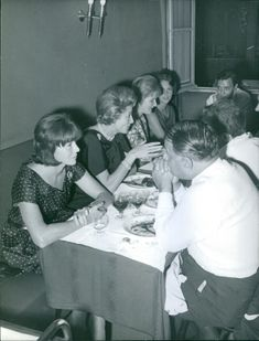 Bettina dining and drinking with other people. 1961
