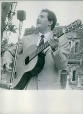 Year ? Domenico Modugno singing on mike and playing guitar.