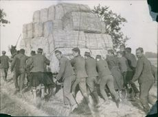Men  pushed a large cart full of hay in Germany. 1914