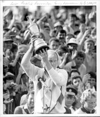 Golf player Greg Norman holds up the trophy after winning the British Open 1986