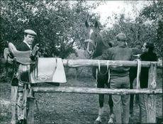 Eddie Constantine in a horse stable with a horse and a man.