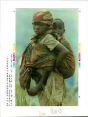 Rwanda war:a hutu girl carrying her little brothar.