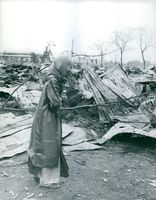 Old lady walking along damaged houses.