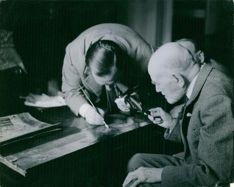 American art historian Bernard Berenson inspecting a painting by a magnifying glass, while a man painting with brush