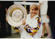 Steffi Graf proudly holds his trophy after winning the Wimbledon Championship
