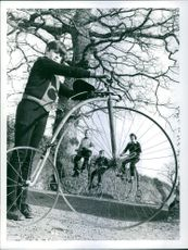 Viewed through the wheel of 13 years old Christopher Thomas' Bike, Mr. and Mrs. Johnny Thomas and 10 year old Robert set put for a spin on their penny farthings. 1976.