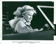 Carroll Baker siting in car.