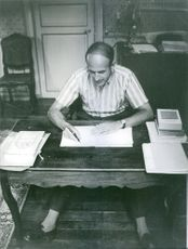 Giscard d'Estaing sitting while writing on the table.