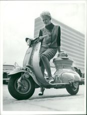 A woman posing with her scooter.