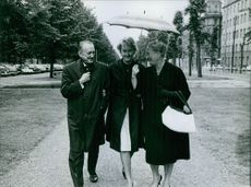 Einar Beyron and his wife Brita Hertzberg walking in street with another woman and talking to her.