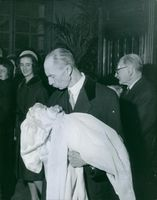 Prince Xavier of Bourbon-Parma holding a baby at a christening, 1962.