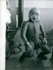 Man siting in the control room, wearing a life suit.