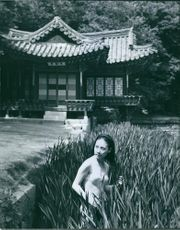 A woman in two-piece poses surrounded by many plants fronting a Japanese house.