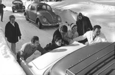 Geraldine Chaplin pushing car with help of other people.