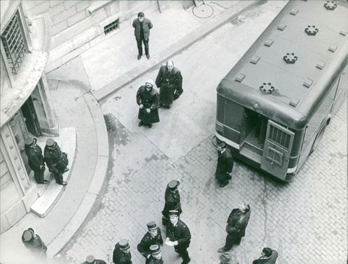 Policemen gathered by a vehicle.