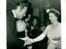 "Queen Elizabeth greets Rex Harrison at the premiere of ""Doctor Dolittle"""