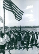 People walking together, passing by flag.