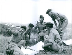 Year ?  A photo of a soldiers siting and indicating something in a grassland.