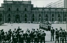 Soldiers gathered in front of a building, common people watching on the side.