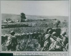 Russian gunners shelling an enemy strong-point while their infantry advance to capture a village, 1942.