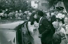 A newly wed couple kissing each other with their guests around them.  Taken - 20 June 1967
