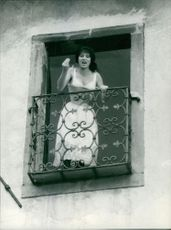 Silvana Mangano standing on balcony and shouting.