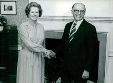 Menachem Begin shaking hand with Margaret Hilda Thatcher, smiling.