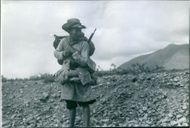 A man standing on the mountain, holding luggage and gun.