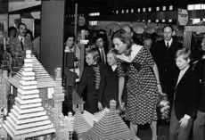 Queen Paola of Belgium with her children, Prince Philippe, Princess Astrid and Prince Laurent, looking at the model of an edifice. 1972