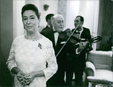 Mala  Rubinstein standing elegantly, clasping both her hands while musicians play behind her.