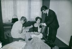 Man feeding a woman and another woman grooming.1960