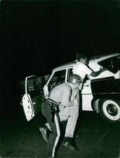Policeman arresting a man in Newark, New Jersey.  Taken - Circa 1967