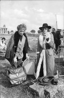 Two women standing with suitcases.