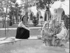 Lee Ann Remick, feeding fishes in a pond.